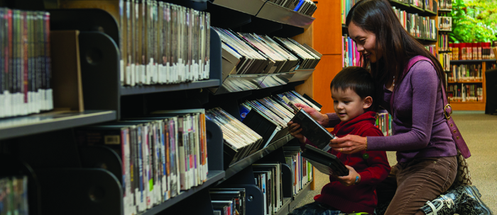 woman and child looking at DVDs shelved at the Library