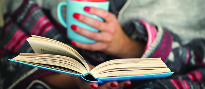 Person reading a book and holding a mug