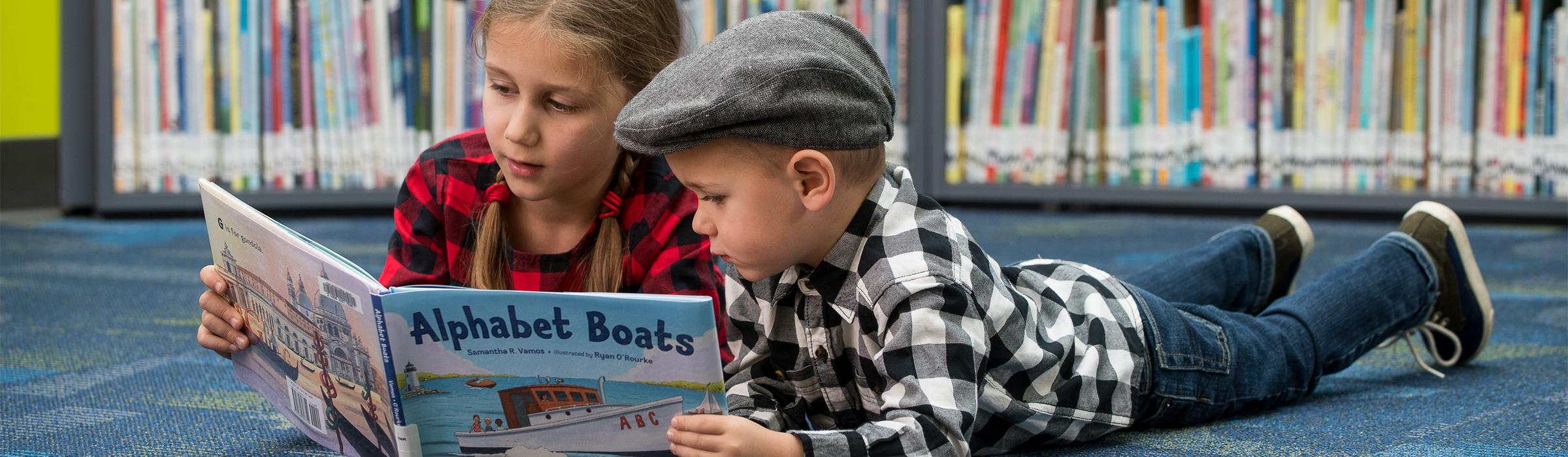 Two children reading a picture book together.