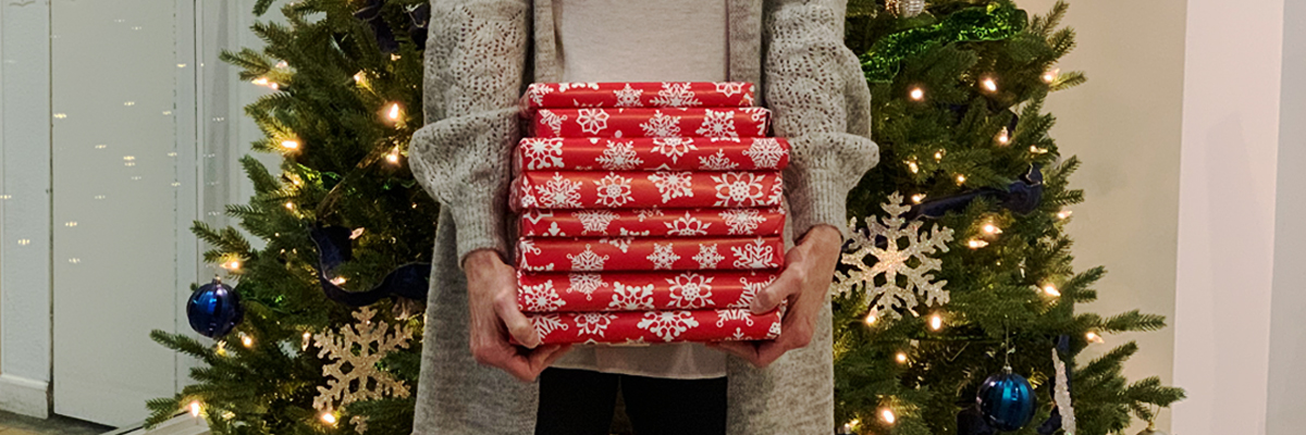 Person holding a stack of gift-wrapped books